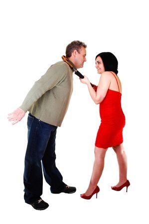 Una mujer en un elegante vestido rojo tirando de su marido con un mans paraguas a su auto para obtener un beso, sobre fondo blanco.  Foto de archivo - 6454438