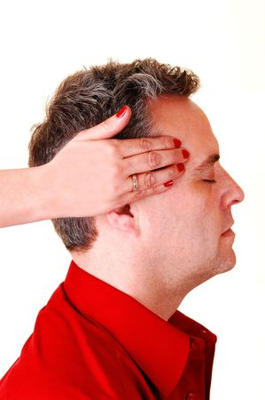 A woman with red fingernails is massaging the head of a middle age man in  a red shirt with a bad headache. Stock Photo - 6519369