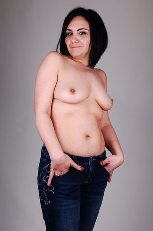 A middle age woman standing topless and in jeans in the studio for light gray background. Stock Photo - 6519366