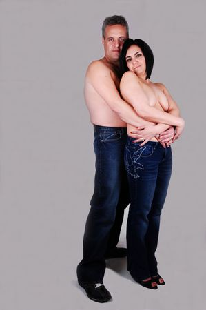 A middle age couple in jeans standing in the studio and hugging each  other for light gray background. photo