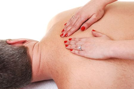 A middle age man with light gray hair getting a upper back massage from a woman with bright red finger nails. He is lying on a white towel. photo