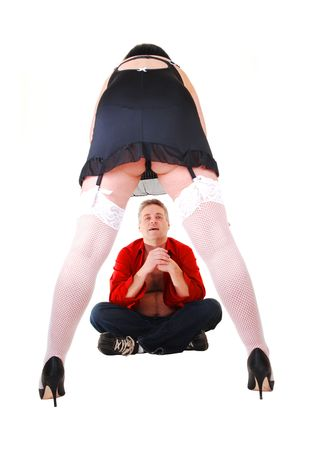 A man sitting on the floor in front of a woman in black lingerie and white stockings with high heels for white background. photo