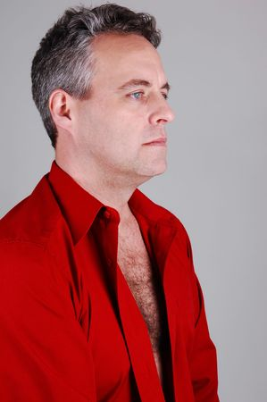 A portrait of a middle age man with light gray hair, closeup in a red shirt in the studio, for light gray background. photo