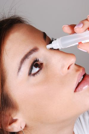 The face of a young pretty woman putting eye drops in her dry eyes to. get relief for her irritated eyes. Stock Photo