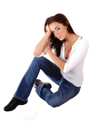 A young pretty sad looking girl sitting on the floor, holding her head, in  jeans and running shoos, for white background. photo