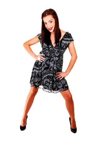 A young woman standing in the studio for white background in a black white dress, brunette hair and high heels.  Stock Photo - 6723399
