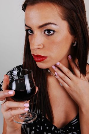 A young beautiful woman with a glass of wine in her hand and in a white black dress and red lips for light gray background. Stock Photo - 6723422