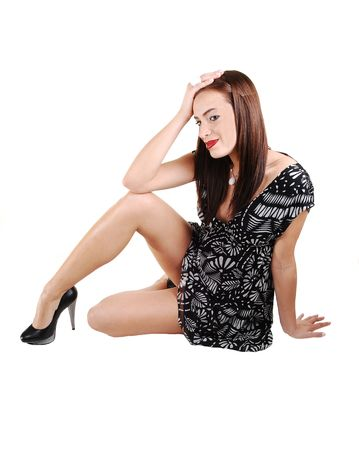 A young lovely woman in a black white dress, sitting on the floor in the studio  for white background and shooing her nice long legs in high heels. Stock Photo - 6723405