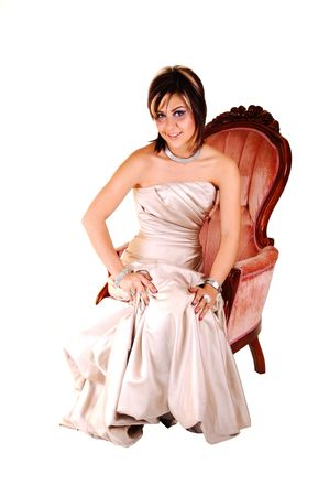 A very pretty young lady in a long beige evening gown sitting in a pink antique  armchair for a portrait, on white background. Stock Photo - 6764243