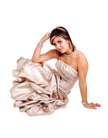 An young lovely woman in a long beige evening dress sitting in the studio on the floor for a portrait, for white background. Stock Photo - 6764238