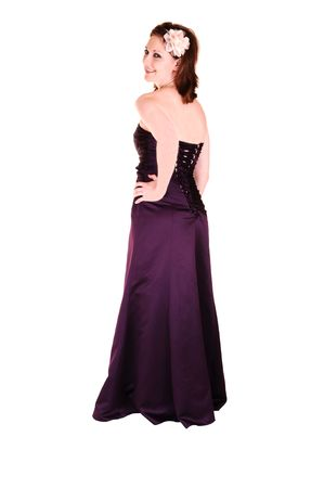 An beautiful young woman in an burgundy long evening gown standing in the  studio, looking over her shoulder for white background. photo