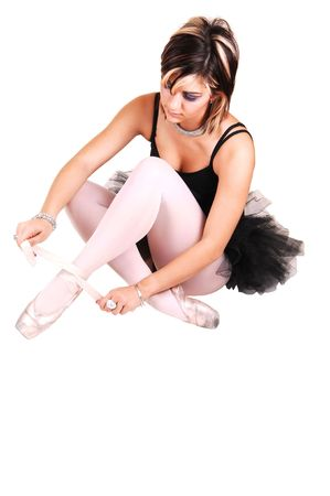 An very pretty young ballerina sitting on the floor in the studio and tying her ballet slippers in a black twill dress and white pantyhose, for white background. Stock Photo - 6764240