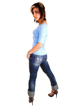 A pretty tall young girl standing with her back to the camera, shooing her nice butt, in high heels, jeans and blue sweater for white background. Stock Photo - 6764241