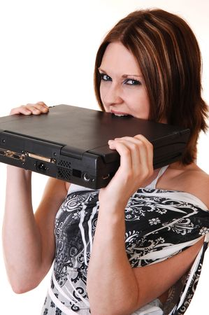A young woman in a white black dress is very angry at her laptop und like to bite the computer so that he is working again, for white background. Stock Photo - 6764250