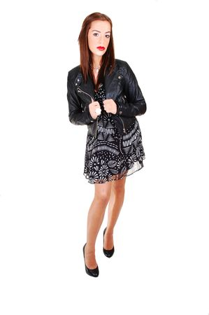 A pretty young woman standing in the studio for white background in a black white dress and black leather jacket and red lips. photo