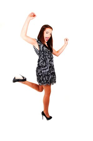 A young woman dancing in the studio for white background in a black white dress, brunette hair and high heels. Stock Photo - 6764257