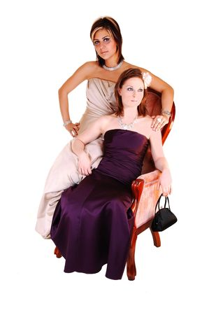 Two young girls and close friends, sitting in a pink antique armchair in long evening gowns, burgundy and beige, in the studio for white background. Stock Photo - 6764264