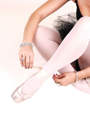 An very pretty young ballerina sitting on the floor in the studio and tying her ballet slippers in a black twill dress and white pantyhose, for white background. photo