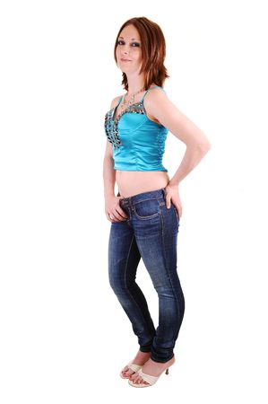 butt tight jeans: An young woman in jeans and a nice blue tight top, shooing her flat stomach and one hand on her butt, for white background. Stock Photo