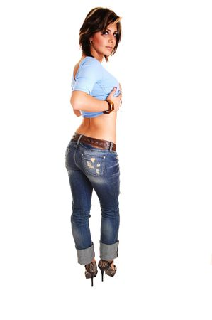 A pretty tall young girl standing with her back to the camera, shooing her nice butt, in high heels, jeans and blue sweater for white background. photo