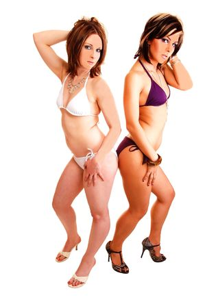 Two bikini woman and close friends, standing in the studio in high heels, both  both holding there hands in the hair, for white background. photo