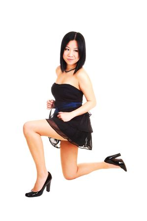 An beautiful young Asian girl kneeling in the studio in a black short dress and high heels for white background.  photo