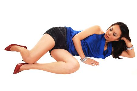 short shorts: A young Asian woman lying on the floor in the studio in red high heels, jeans shorts and a blue blouse, for white background.