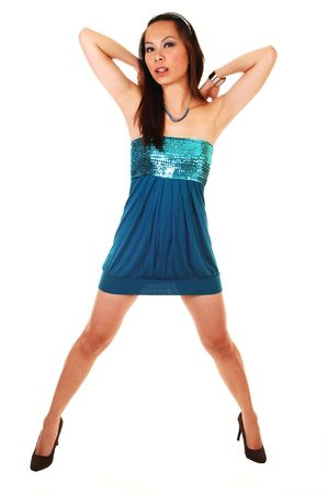 apart: A young Asian woman standing in a studio in an short blue dress and high heels, her arms behind her head, for white background. Stock Photo