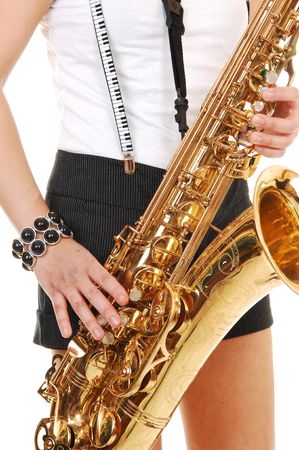 suspender: A young Asian woman standing in the studio, playing the saxophone in shorts with suspender, in closeup, for white background. Stock Photo