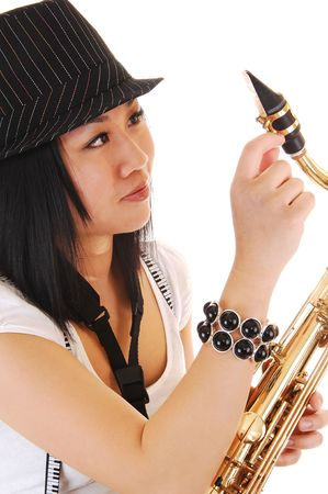 suspender: A young Asian woman with a hat on her black hair,  fixing her saxophone in a closeup picture, for white background. Stock Photo