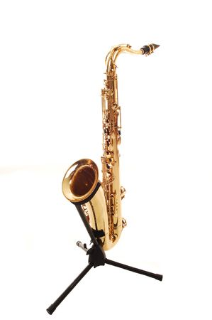 A beautiful brass saxophone on an black rack sitting on the floor of a studio for white background. Stock Photo - 6848664