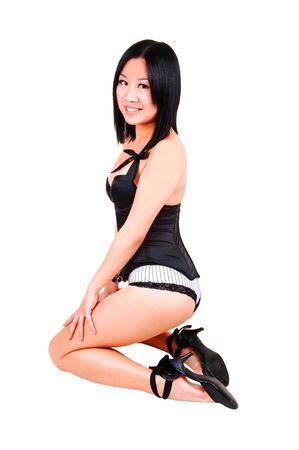 Young Chinese woman kneeling on the floor in the studio in black high heels and black and white lingerie, smiling into the camera, on white background. photo