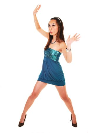 A young Asian woman standing in a studio in an short turquoise dress and high heels, her arms up in the air, for white background. photo