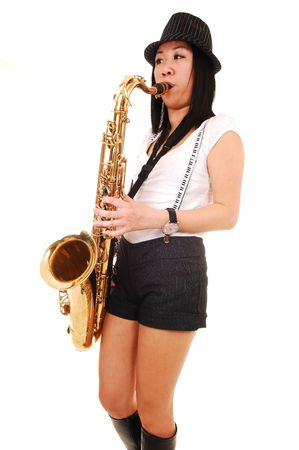 A young Asian woman standing in the studio, playing the saxophone in shorts with suspender and a hat on her black hair, for white background. photo
