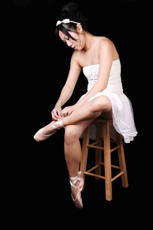 A Chinese ballet dancer in a white dress sitting on a chair and tying her ballet slippers, for black background. photo