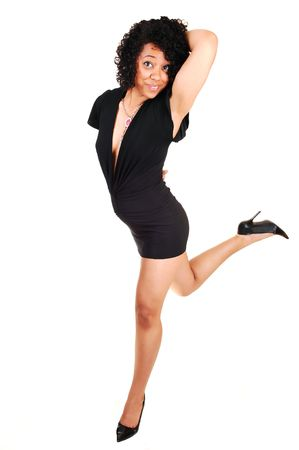 sexy girl dance: A beautiful young Hispanic woman, in a black short and tight dress and high heels is dancing in the studio, for white background.