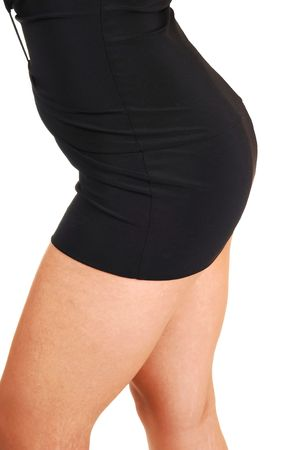 The nice round bottom of a young woman in a short tight black dress, with nice legs, standing in the studio for white background. photo