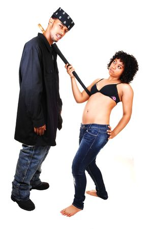 An young Hispanic woman pulls her black boyfriend with an umbrella down to her. She in jeans and black bra and bare feet, he in jeans and a  very long black shirt and a head scarf, for white background. photo