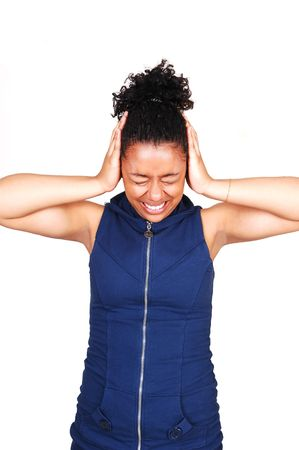 A young Hispanic girl standing in a very noisy place and covering her ears with her hands, in a blue dress with a zipper in front, for white background. photo