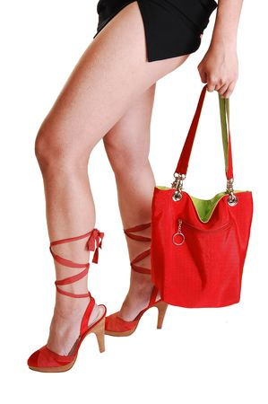 foot gear: The beautiful long legs of a young woman in a short black skirt and a red handbag with green lining and red high heels with long laces for  white background.