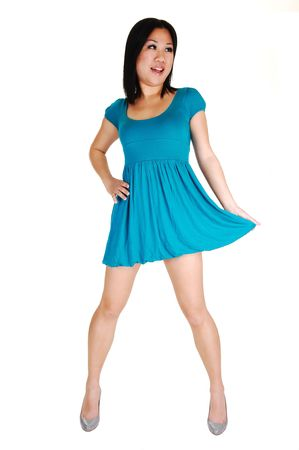 A young pretty Asian woman in a light blue short dress and high heels standing in the studio, pulling on her dress, for white background. Stock Photo - 6957294