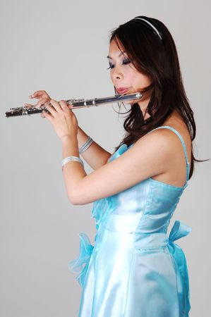 A young Asian woman in an light blue evening dress playing the flute standing in the studio for light gray background. photo