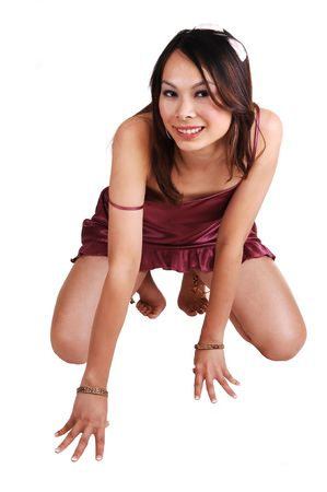 A young Chinese girl in burgundy lingerie kneeling in the studio on the floor bare feet, for white background. photo