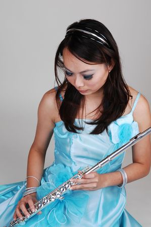 A young Asian woman in an light blue evening dress holding the flute standing in the studio for light gray background. photo