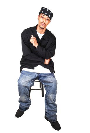 A black man in jeans, way down, and very big and long shirt, with a headscarf, sitting in the studio, for light blue background. photo