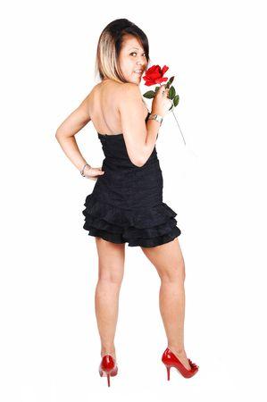 Una mujer joven y bastante asiática en rojos los tacones, un corto vestido de negro y una rosa roja en su posición de mano con su espalda a la cámara, mirando sobre su hombro, sobre fondo blanco. Foto de archivo - 6957367