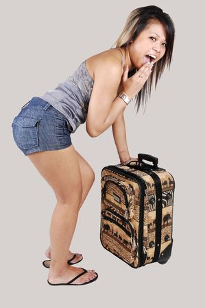 A surprised Asian woman found out she loosed the key to her luggage, standing in shorts and slippers with her bag on light gray background. photo