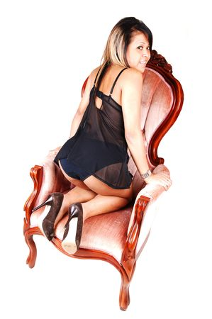 A nice Asian woman kneeling with the back to the camera in a pink old armchair, in black lingerie, smiling and shooing her bum, over white. photo