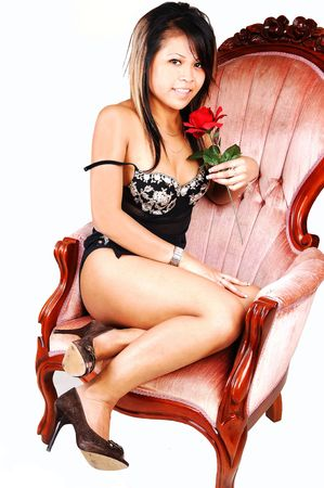 A young Asian woman in black lingerie with a red rose in her hand, sitting in a pink old armchair, with high heels, shooing her nice legs, over white.  photo
