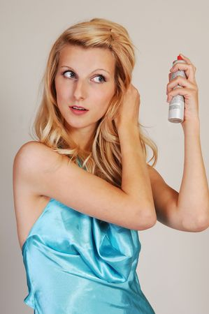 hairspray: A beautiful woman with long blond hair and a light blue dress is fixing her hair with hairspray, for light gray background. Stock Photo